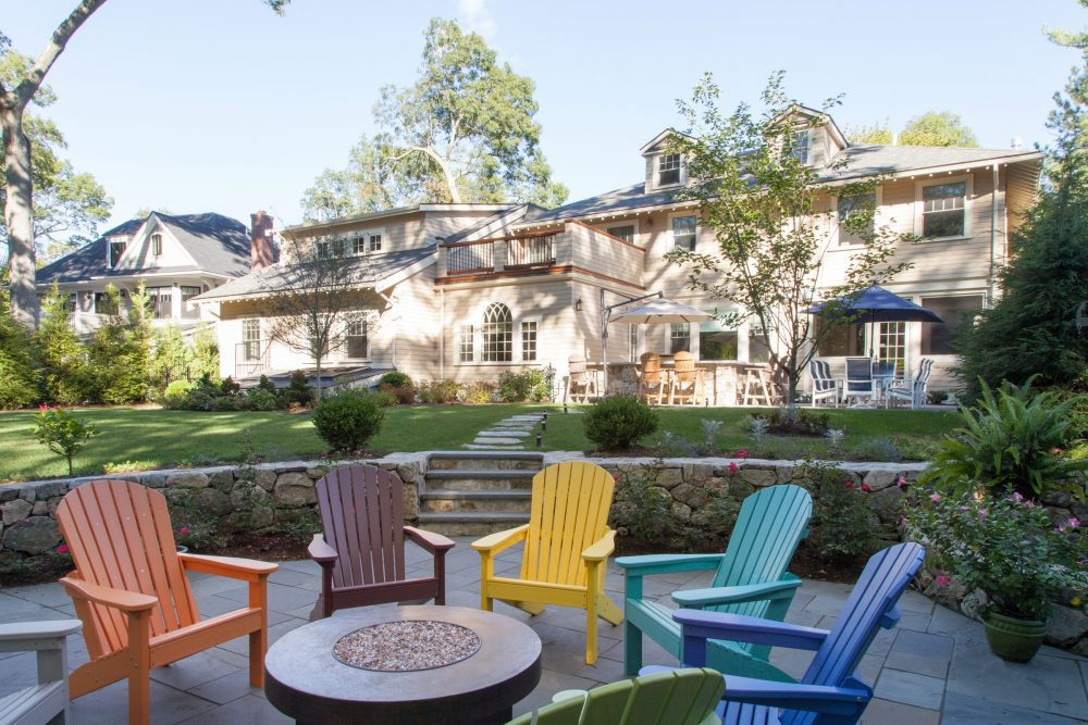 beautiful livable outdoor space with colorful chairs and fire pit